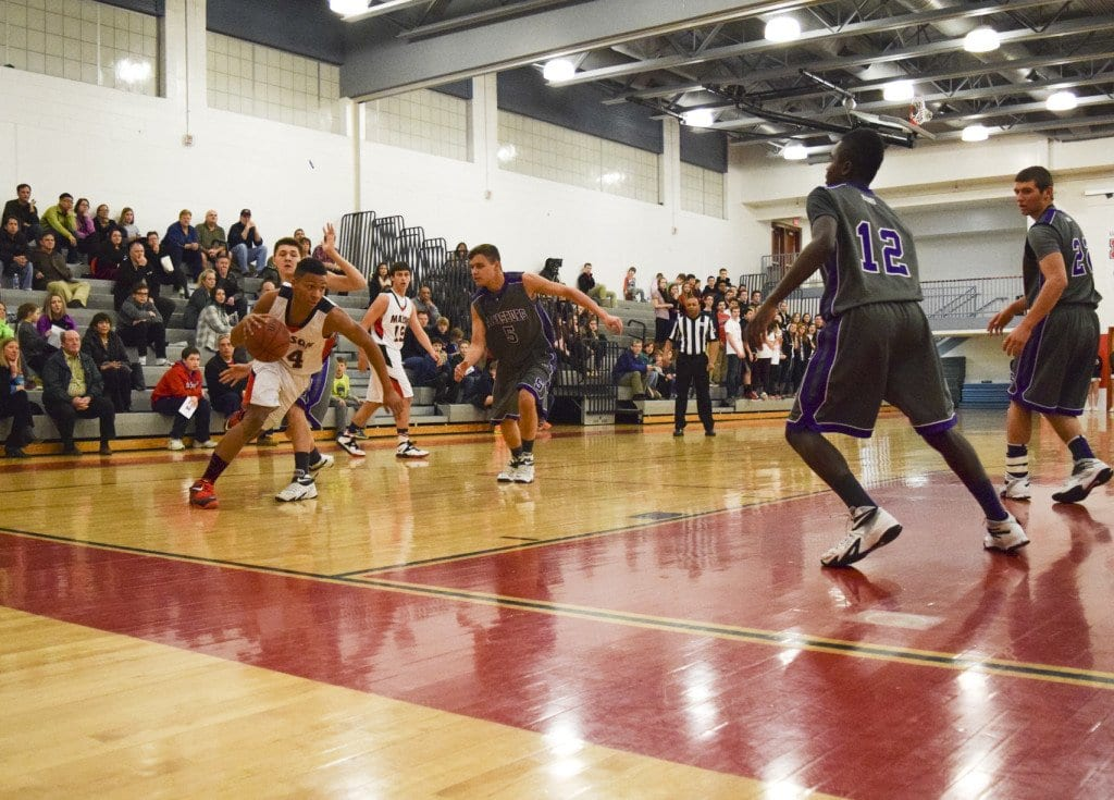 MASON JUNIOR ROBERT TARTT (left) drives the baseline during the Mustangs 54-41 win over Strasburg High School last Thursday. Tartt, who was named the Bull Run District's Player of the Year after the game, led the Mustangs with 18 points and 14 rebounds against the Rams. (Photo: Liz Lizama/News-Press)