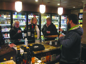 """Three customers at dominion Wine and Beer on West Broad Street sample one of the store's wines. Afsheen Takafor recommends """"Charles & Charles' Red Blend"""" from Washington state. (Photo: Patricia Leslie/News-Press)"""