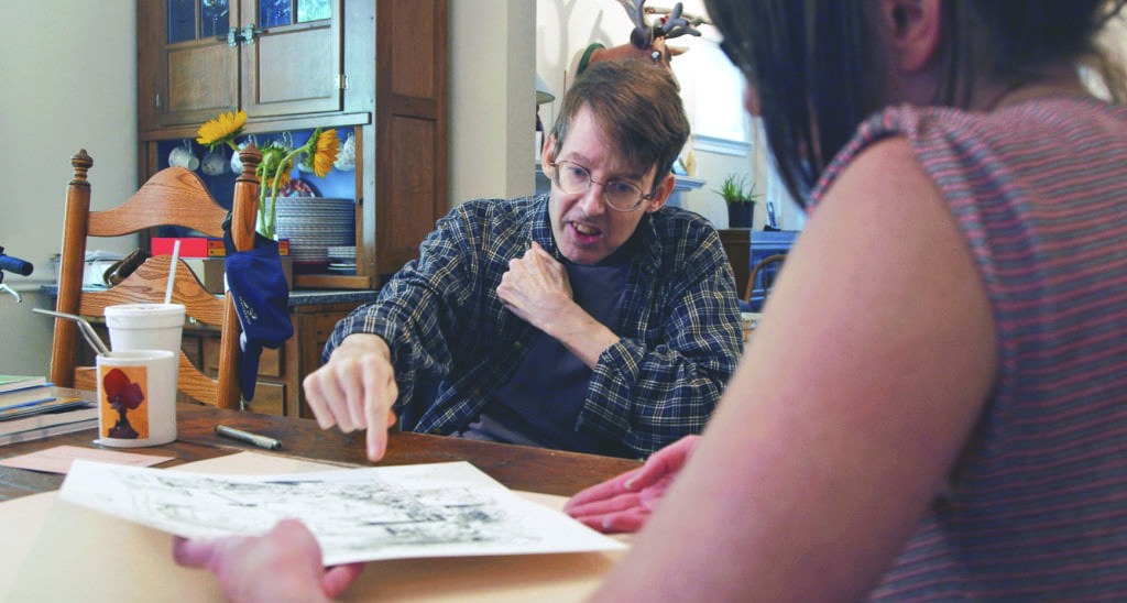 Cartoonist Richard Thompson looks at some of his work in a scene from a new short documentary about his life and his work. (Photo: Courtesy of GVI)