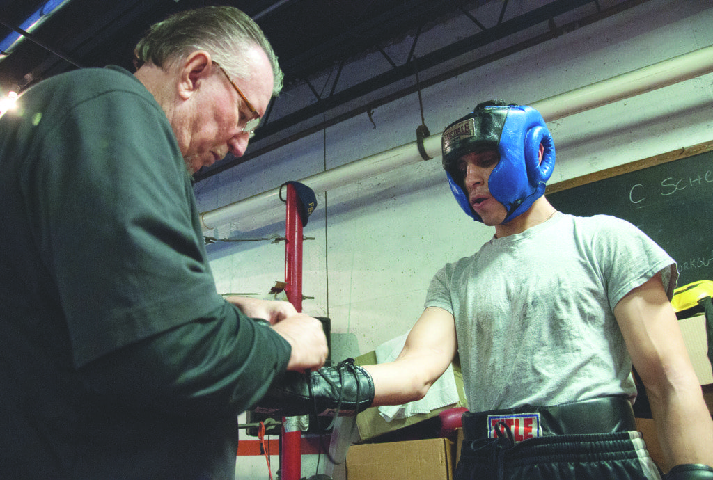 jUAN RODRIGUEZ (right), gets his boxing gloves tied and taped up by his trainer and manager, Jim Ed Jones. Rodriguez is fighting Yurii Polischuk on Saturday at the Patriot Center. (Photo: News-Press)