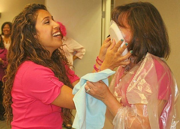 """Medtech College staff Wendy Yupanqui pies campus director Janeth Baron during the Falls Church campus of Medtech College's """"Pie It Forward"""" fundraiser event last Wednesday."""