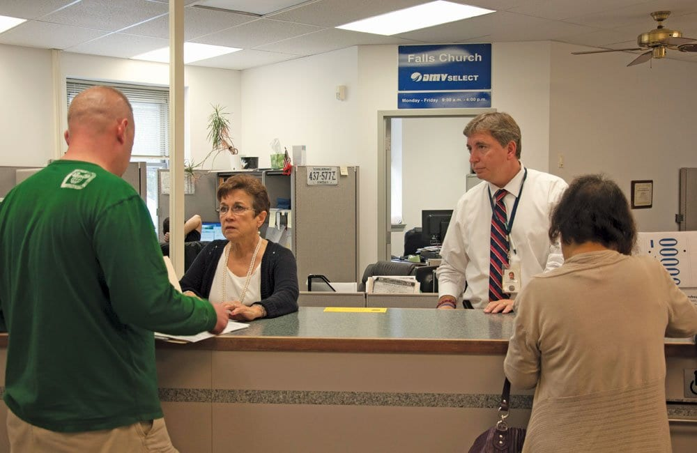 Falls Church Commissioner of the Revenue Tom Clinton (right) helps two DMV Select customers at his office in City Hall. Clinton says he plans to end the DMV Select services his office provides at the end of the month. (Photo: News-Press)