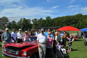 Members of the Bailey's Crossroads Rotary Club stand with the 1966 Mustang they auctioned off. (Courtesy Photo)