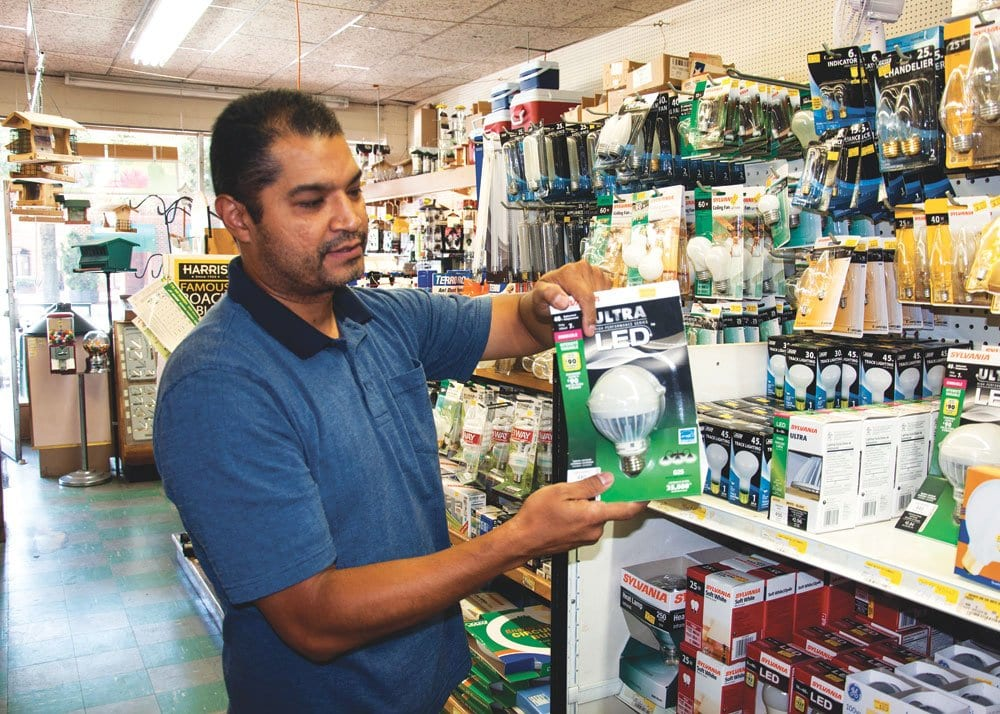 A BROWN'S HARDWARE EMPLOYEE shows off an environmentally-friendly LED lightbulb at the Falls Church store. (Photo: News-Press)