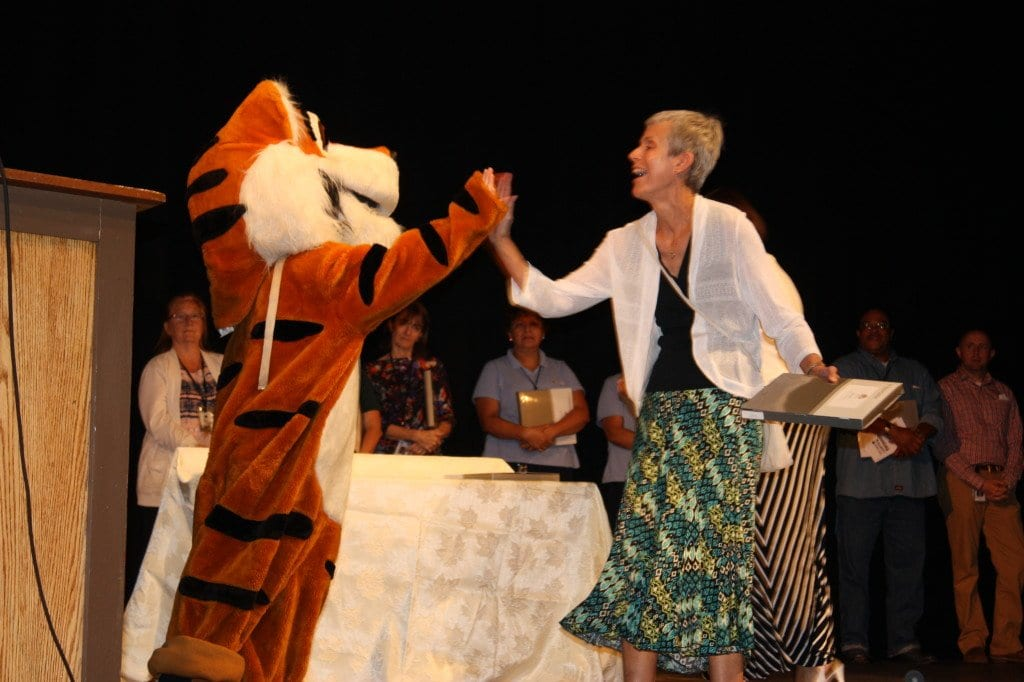 Thomas Jefferson Librarian Helen Heil shares a high-five with a mascot in today's convocation. (Photo: News-Press)
