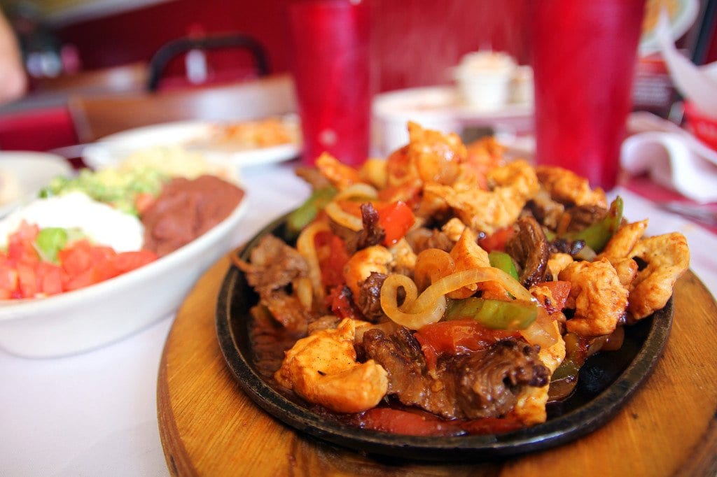 The combo fajitas mix steak, chicken and shrimp on a sizzling iron plate.