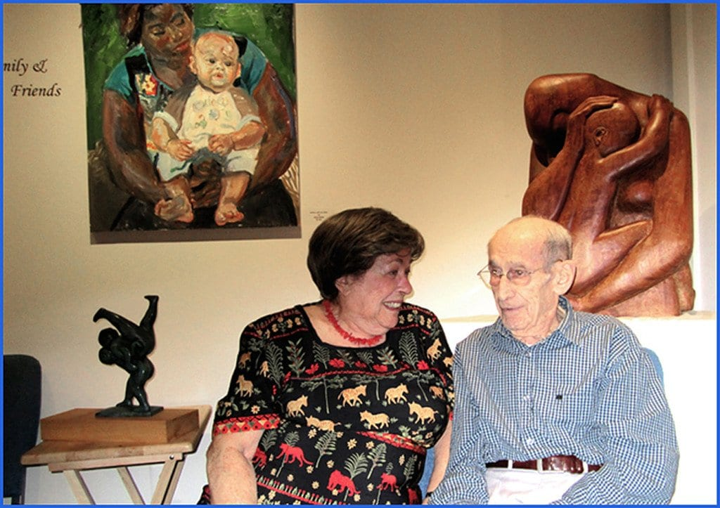 Irene Awret is pictured above with her husband, Azriel, at one of many art exhibitions they held together. His wood-crafted piece is behind him, and Irene's painting piece is behind her.