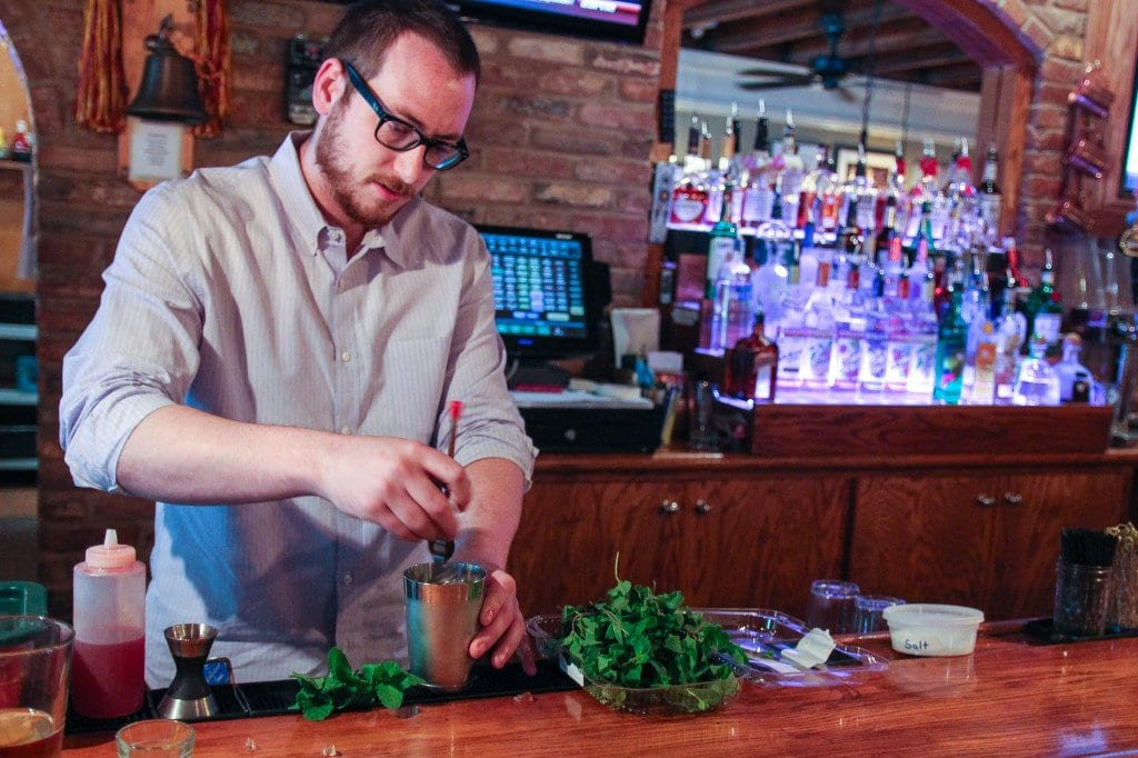 PAUL TAYLOR, the new beverage director for the restaurant group which includes Falls Church's Dogwood Tavern, muddles up some mint for a Virginia julep. (Photo: News-Press)
