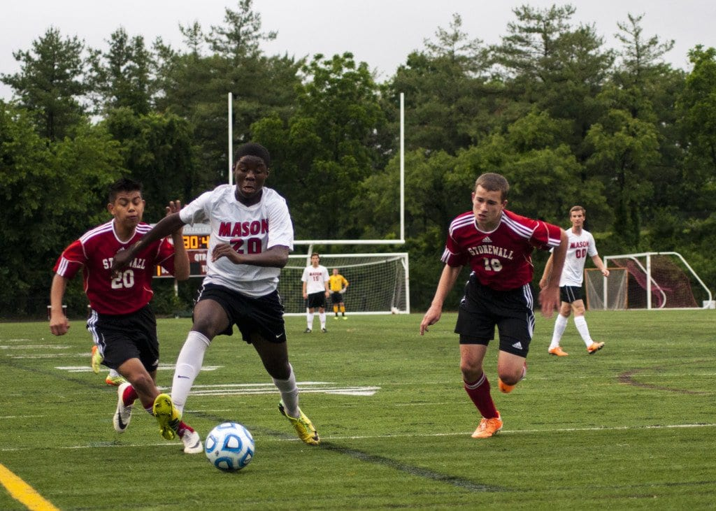 George Mason sophomore striker Raheem Lawal, flanked by two Stonewall Jackson defenders, chases down the ball. Lawal netted a hat trick in the George Mason Mustangs' conference championship win over the Stonewall Jackson Generals. (Photo: Drew Costley)