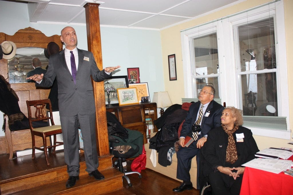 D.C. Mayoral candidate Andy Shallal speaks while, right, his hosts Nikki and Ed Henderson listen intently)