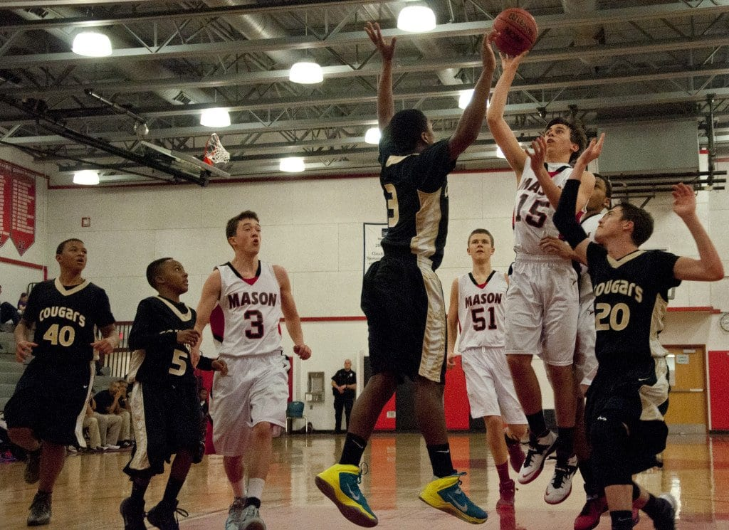 Mason Sophomore guard Elliot Mercado pulls up for a jumper over Manassas Park High School junior guard Marcus Lawson and sophomore forward Sean Kapus.  Mercado led the Mustangs in scoring in both of their district match-ups in the past week. (Photo: Drew Costley)