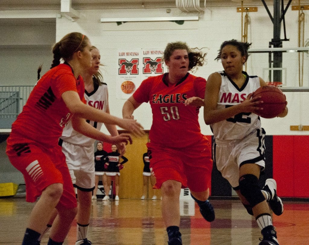 Mason Junior forward Katie Goodwin drives past junior forward Allison Hicks and gets ready to take on junior forward Sydney Chrane.  Goodwin scored eight points in the win against the Eagles. (Photo: Drew Costley)