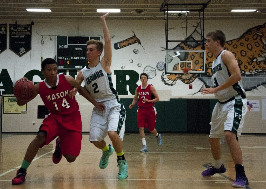 Sophomore Robert Tartt attempts to dribble around Falls Church senior guard Chris Devlin.  Tartt led the Mustangs in scoring with 15 points against the Jaguars. (Photo: Drew Costley)