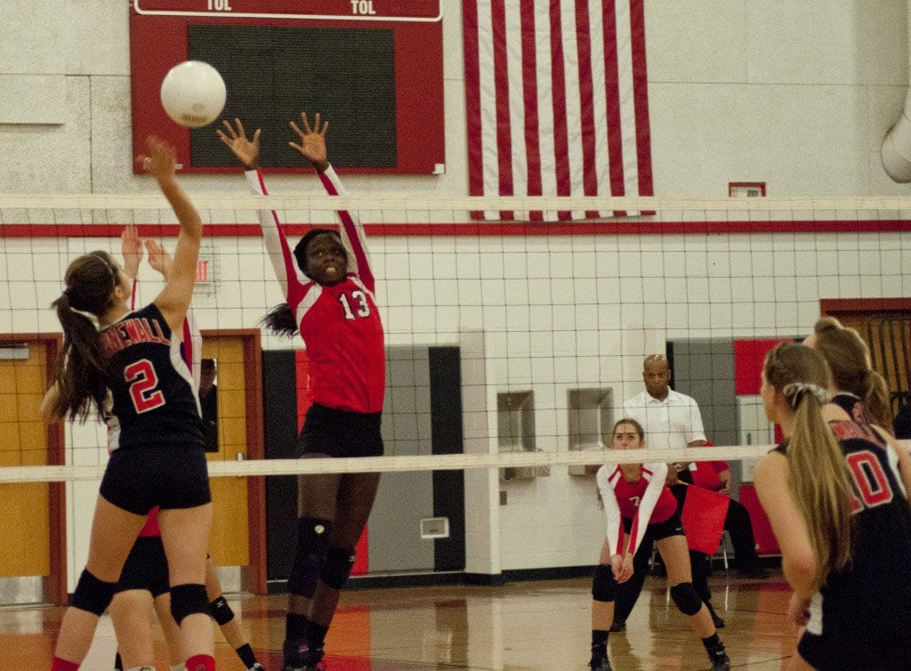 Sophomore middle hitter Vicky-Marie Addo-Ashong attempts to block a spike by a Stonewall Jackson player while senior defensive specialist Peggy Brozi prepares for an underhand dig. (Photo: Drew Costley)