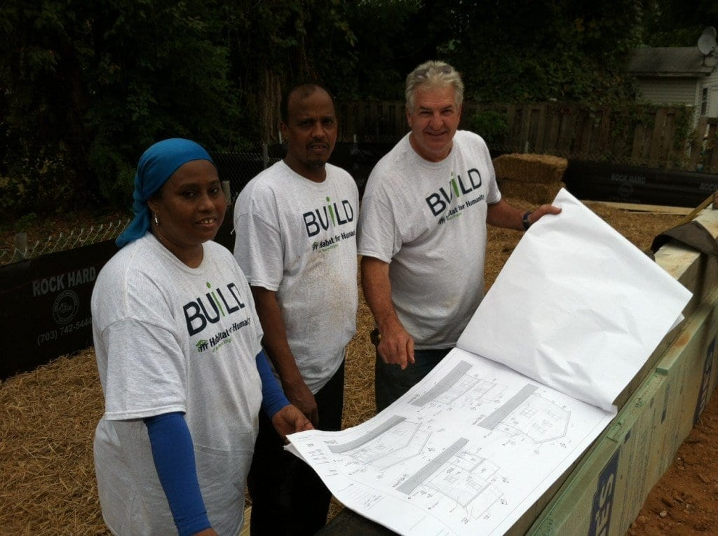 Amani Salih (left) and Muhsin Khalil (center) examine plans for their new home with a Habitat for Humanity volunteer. (Photo: Courtesy Jon Smoot)