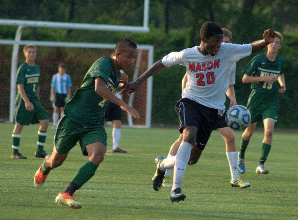Freshman striker Raheem Lawal evades a Nelson County defender while moving down field.  Lawal is the Mustangs' leading scorer and second in the region in scoring. (Photo: Drew Costley)
