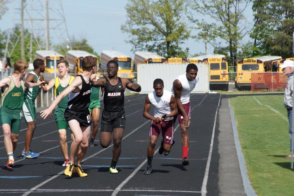Michael Addo-Ashong passes the baton to Truman Custer for the final leg of the 4x400 relay that qualified the team for the state meet with a time of 3:38.16. (Photo: Carol Sly)