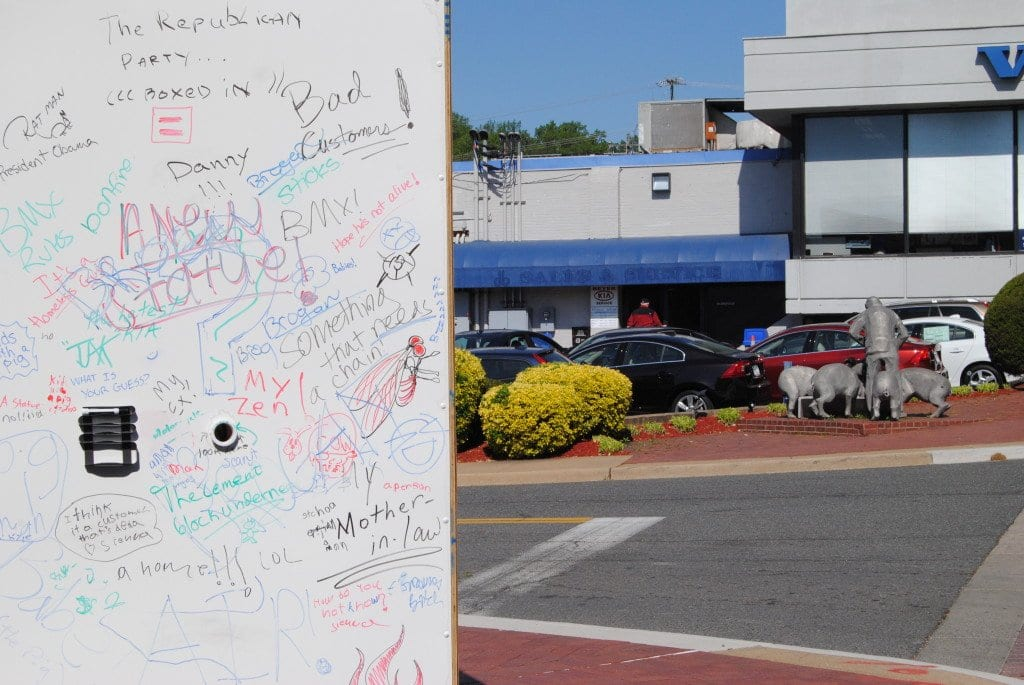 Whiteboard walls surround the new sculpture outside of Beyer Kia, across the street from Don Beyer Volvo's iconic pig statue. Visitors are invited to peer into holes in the walls and guess what the new sculpture might be, recording their answers on the walls. The new statue will be unveiled Friday.  (Photo: News-Press)