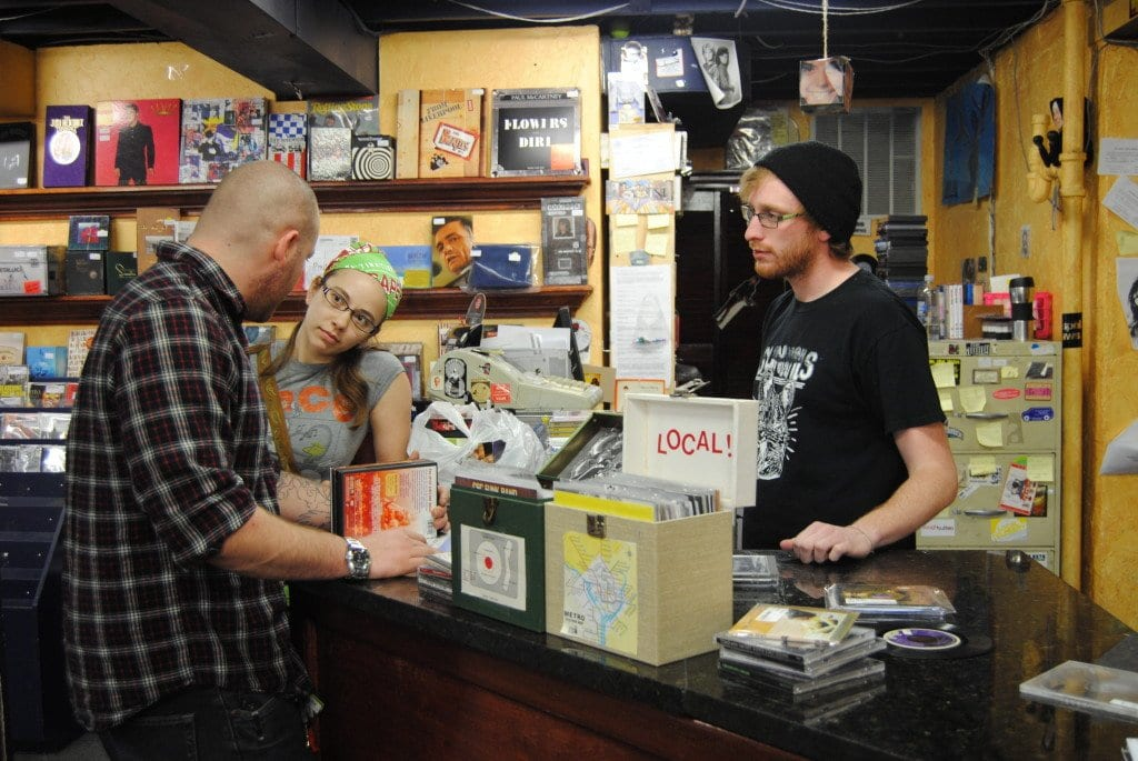 CD Cellar patrons discuss selling some of their DVDs. Much of the store's stock is brought in by customers looking to sell or trade in items. (Photo: News-Press)