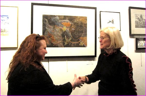 """Printmaking show winner Jacqlyn Sickler (left) is congratulated by show juror  Lisa Kuhn.  Sickler's winning entry is the large woodcut """"Natural Woman,"""" shown between the two. """"I thought the winning print by Jacqlyn Sickler was impressive,""""  said the juror. """"The woodcut process is very challenging.  Her use of one block to create her print is difficult, leaving little room for error.  Her print was well executed, the composition and use of color were interesting, and the scale of the print was impressive."""" (Photo: Shaun van Steyn)"""